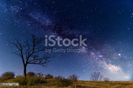 962814924 istock photo Milky way galaxy with stars and space dust in the universe over the hill 1147997726