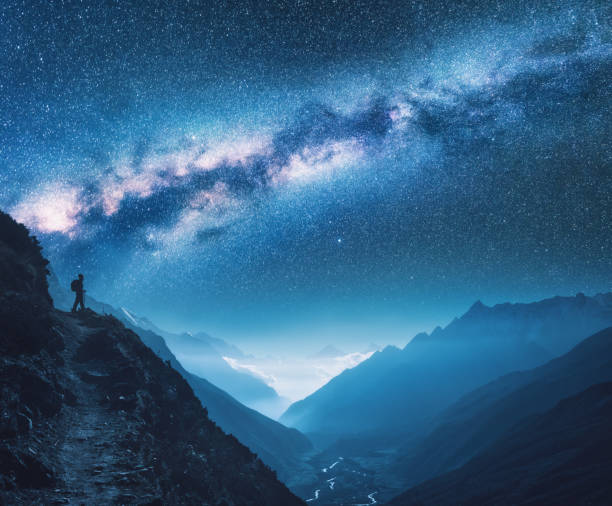 milky way, girl and mountains. silhouette of standing woman on the mountain peak, mountains and starry sky at night in nepal. sky with stars. trekking. night landscape with bright milky way. space - den belitsky foto e immagini stock