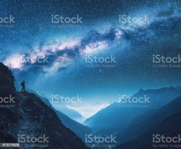 Photo of Milky Way, girl and mountains. Silhouette of standing woman on the mountain peak, mountains and starry sky at night in Nepal. Sky with stars. Trekking. Night landscape with bright milky way. Space