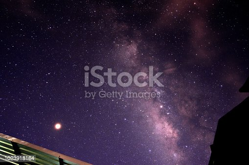 653506436istockphoto Milky way glaxy and stars with house roof top. 1023918164