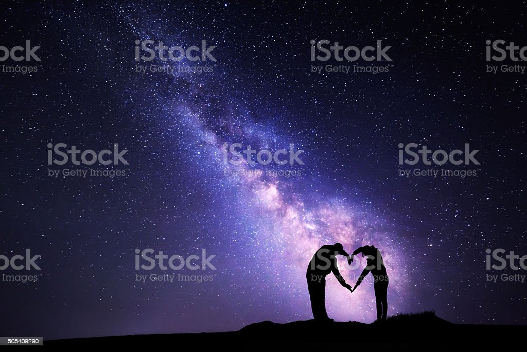 Milky Way. Man and woman holding hands in heart shape bildbanksfoto