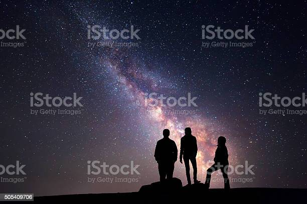 Milky Way. Night sky and silhouette of a family Milky Way. Night sky with stars and silhouette of a happy family with raised-up arms Activity Stock Photo