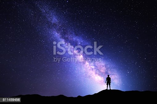 istock Milky Way. Night sky and silhouette of a standing man 511459456