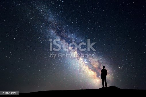 istock Milky Way. Night sky and silhouette of a standing man 513298210