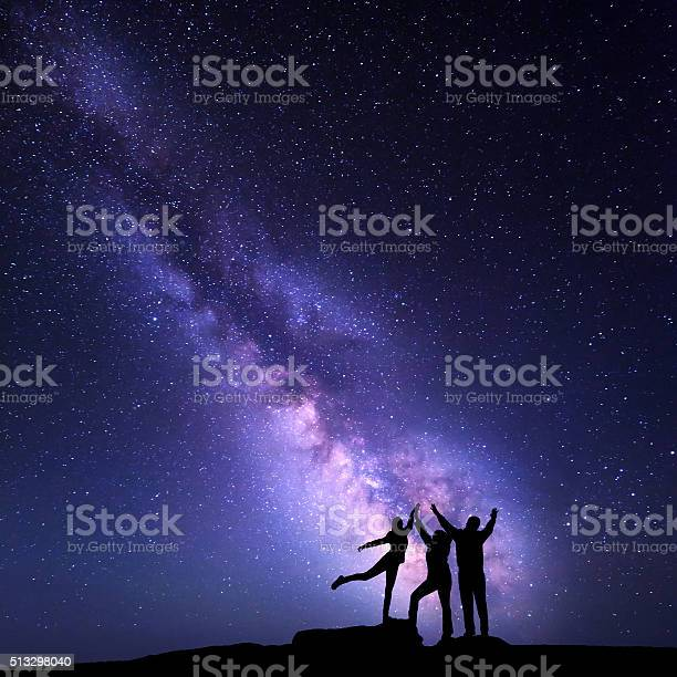 Photo of Milky Way. Night sky with silhouette of a happy family