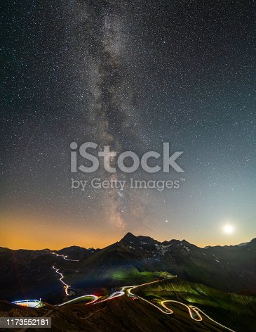 istock milky way on sarry night sky over mountain peak and winding road with light trails 1173552181