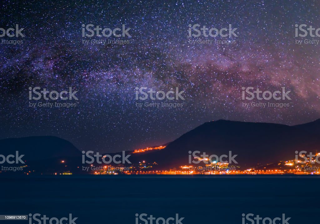 milky way on the night sky above a night sea bay town
