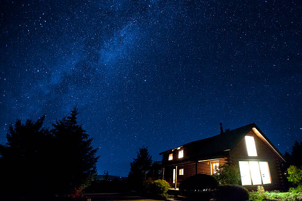 Milky way over a cozy cabin stock photo