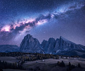 Milky Way over beautiful mauntains at night. Autumn landscape with mountains, purple sky with stars and bright milky way, buildings, trees, high rocks. Alpe di Siusi in Dolomites, Italy. Space