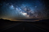 Beautiful night sky with the milky way over an empty road in Death Valley National Park. Clear sky, no lights and no People. Viewpoint from the middle of the Road. California, Southwest USA.