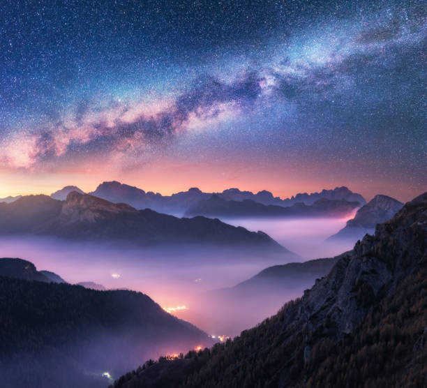 milky way over mountains in fog at night in summer. landscape with alpine mountain valley, purple low clouds, colorful starry sky with milky way, city illumination. passo giau, dolomites, italy. space - den belitsky foto e immagini stock