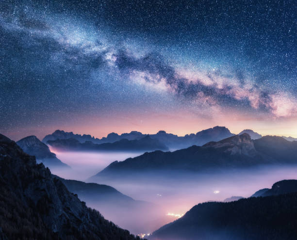 milky way over mountains in fog at night in summer. landscape with foggy alpine mountain valley, purple low clouds, colorful starry sky with milky way, city illumination. dolomites, italy. space - den belitsky foto e immagini stock