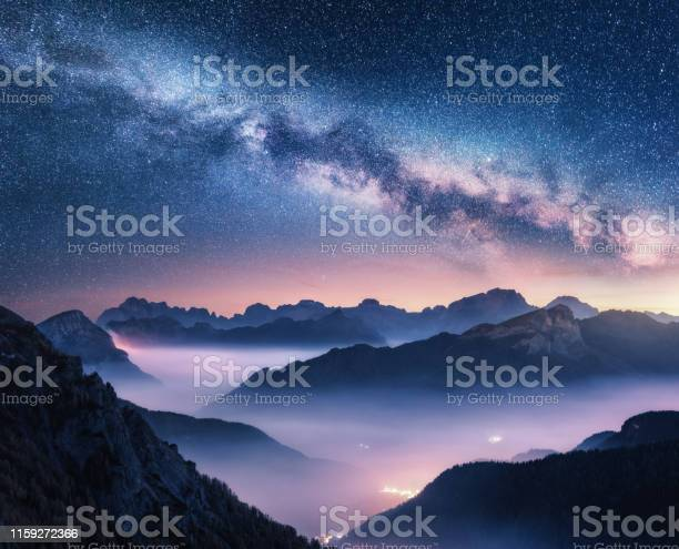 Photo of Milky Way over mountains in fog at night in summer. Landscape with foggy alpine mountain valley, purple low clouds, colorful starry sky with milky way, city illumination. Dolomites, Italy. Space