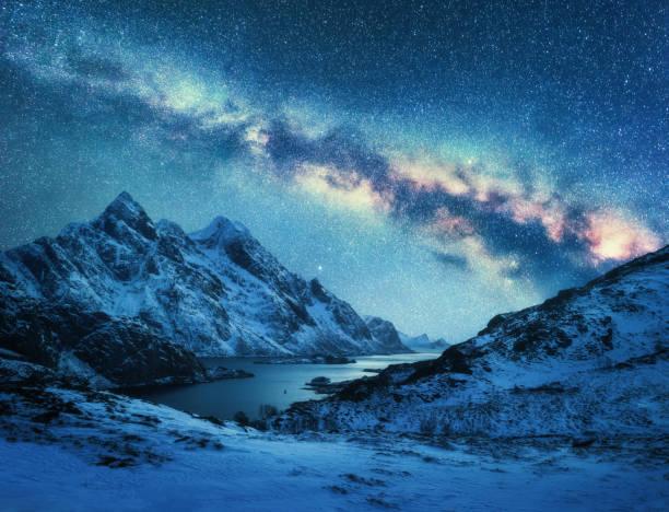 Milchstraße über Schnee bedeckt Berge und Meer in der Nacht im Winter in Norwegen.  Landschaft mit schneebedeckten Felsen, blauer Himmel, bunte Galaxie, wunderschönen Fjord. Lofoten Inseln, Norwegen. Raum – Foto