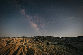 Milky Way at Night over Death Valley National Park Zabriskie Point. Night view over the Ridges and Gullies at Golden Canyon at Night with a clear star sky, Zabriskie Point, Death Valley National Park, California, USA, North America