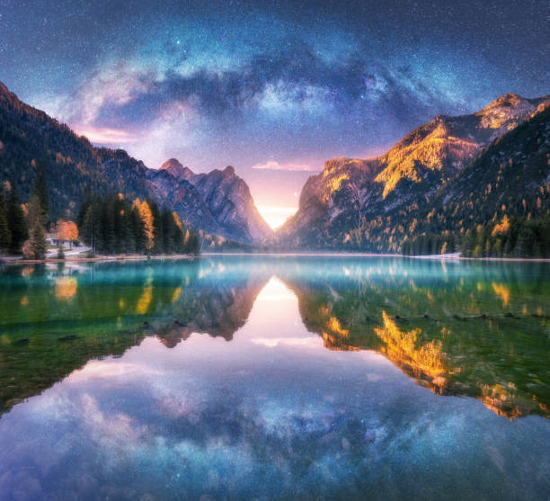 Milky Way reflected in water in mountain lake at starry night. Autumn landscape with purple sky with stars, blue fog, reflection, trees with colorful leaves, rocks in fall at sunset. Space and galaxy stock photo