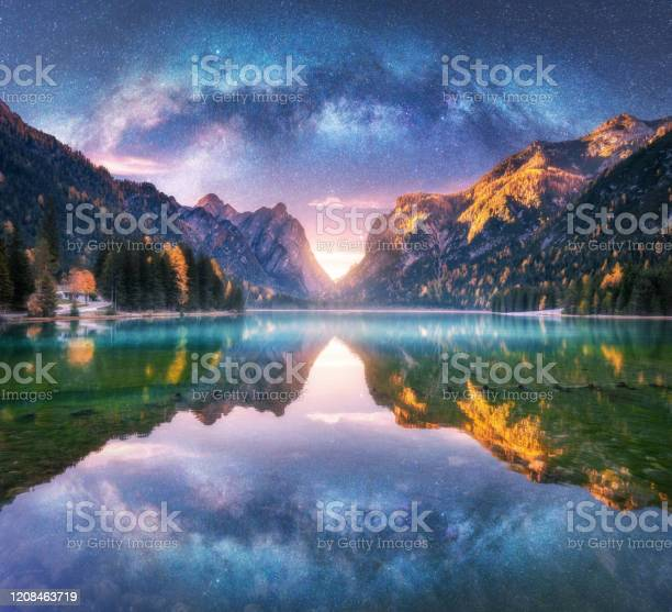 Photo of Milky Way reflected in water in mountain lake at starry night. Autumn landscape with purple sky with stars, blue fog, reflection, trees with colorful leaves, rocks in fall at sunset. Space and galaxy