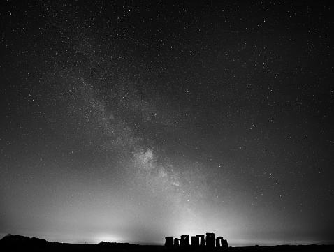 Monochrome landscape of the Milky Way (our galaxy) rises to display it's core over the ancient stone circle  in Wiltshire, UK