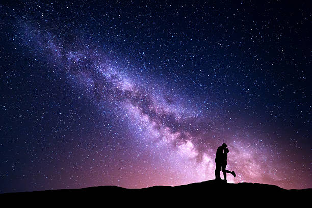 milky way. silhouettes of hugging and kissing man and woman - den belitsky foto e immagini stock