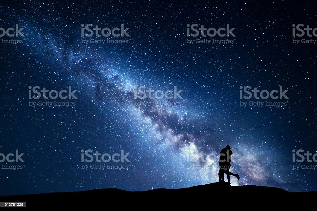 Milky Way. Silhouettes of hugging and kissing man and woman stock photo