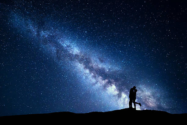 milky way. silhouettes of hugging and kissing man and woman - romantische spitze stock-fotos und bilder