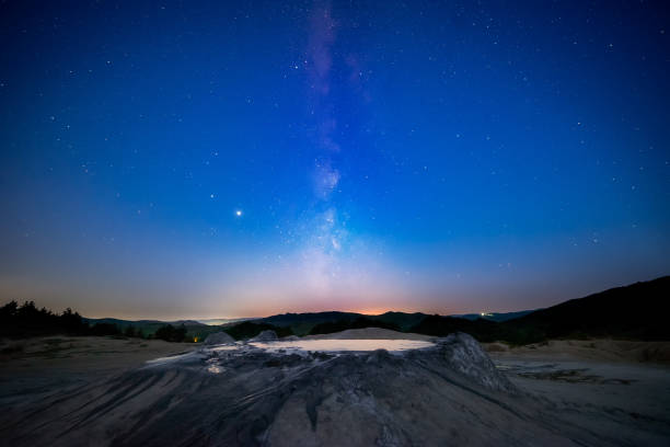 Milky way starry sky fading away into morning light with a muddy volcano in the foreground shot in Romania, Buzau County at Muddy Volcanoes Vulcanii noroiosi stock photo