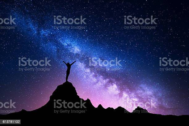 Photo of Milky Way with  silhouette of a standing happy girl