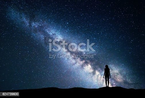 Milky Way with standing woman. Colorful landscape with night sky with stars and silhouette of a girl on the mountain on the background of beautiful galaxy. Blue milky way. Travel. Bright stars