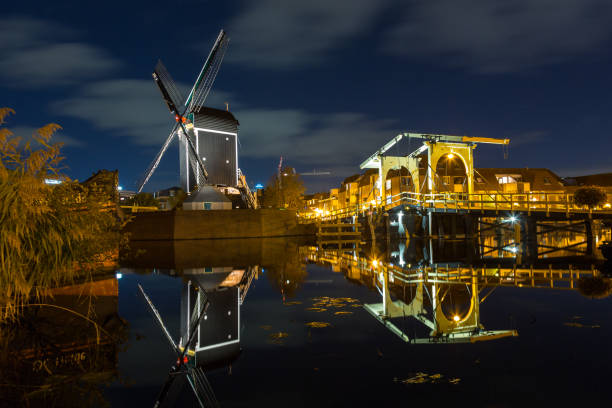 Mill and Rembrandt bridge in Leiden Mill de Put and the Rembrandt bridge in Leiden by night and reflection in the river Rijn in LEIDEN, THE NETHERLANDS leiden stock pictures, royalty-free photos & images