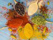 Milled spices - garlic, turmeric, paprika, anise, oregano, cardamom.  Round of golden spoons on  blue wooden table. Top view, close-up