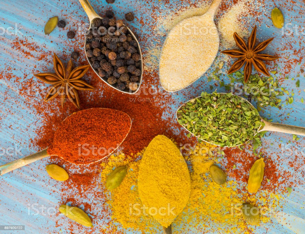 Milled spices - garlic, turmeric, paprika, anise, oregano, cardamom.  Round of golden spoons on  blue wooden table. Top view, close-up stock photo