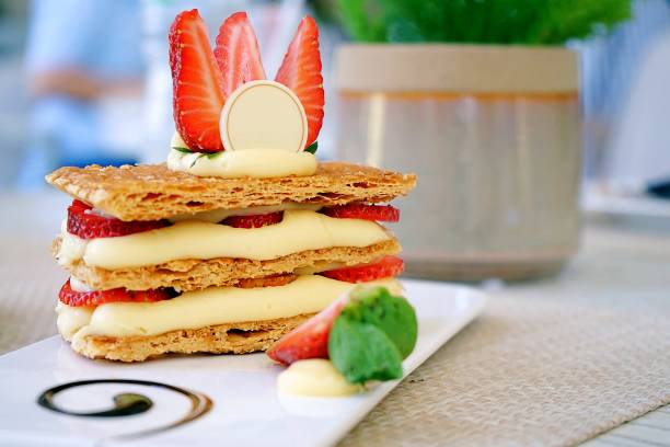 Mille-feuille, that's the French desserts, is a stack of pie crust, custard cream and fresh strawberry then topped with strawberry and white chocolate. - fotografia de stock