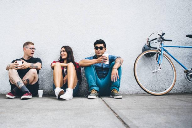 tausendjährigen radfahrer im städtischen umfeld - freundin tattoos stock-fotos und bilder