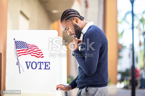 A millennial black man voting at a voting booth in an election.