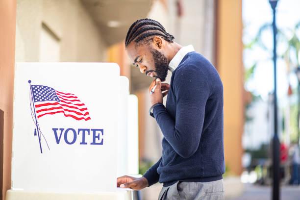 millenial black man voting in election - выборы президента стоковые фото и изображения
