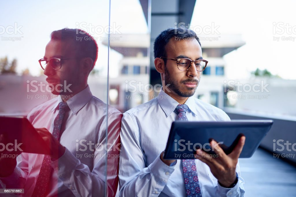 Millenial businessman leaning confidently on a dark glass wall with cityscape background – Foto