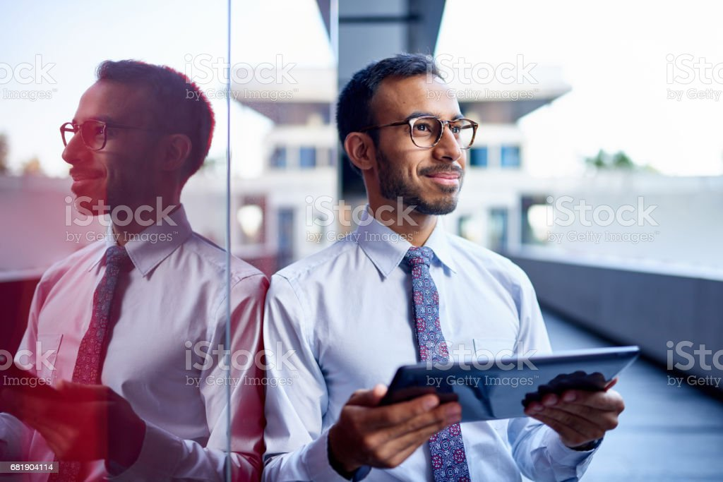 Millenial businessman leaning confidently on a dark glass wall with cityscape background stock photo