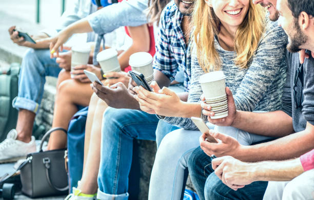 Millenial friends group using smartphone with coffee at university college - People hands addicted by mobile smart phone - Technology concept with always connected trendy millennials - Filter image stock photo