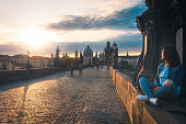 Beautiful brunette girl, in casual clothes, relaxing and enjoying the sunrise on the Charles Bridge walls, in Prague city, Czech Republic.