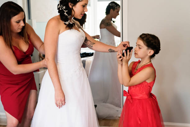 Millenial woman putting on her wedding dress. stock photo