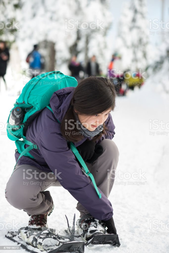 Millenial Woman with Backpack Strapping on Snowshoes at Park Entrance stock photo