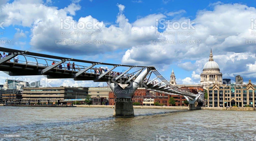 Millenium Bridge in London Millenium Bridge on Thames river with St Pauls Cathedral in the back, London, United Kingdom. Architectural Dome Stock Photo