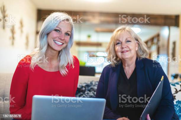 Millennial Adult Female And Mature Adult Female Sitting On Couch Using Laptop Technologymothers Day Photo Series Stock Photo - Download Image Now