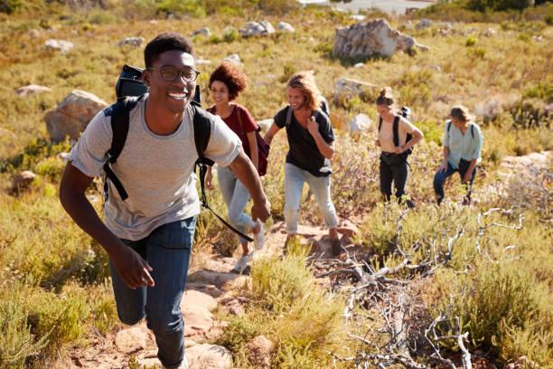 millennial hombre afroamericano que lleva amigos de excursión archivo único cuesta arriba en un camino en el campo - excursionismo fotografías e imágenes de stock