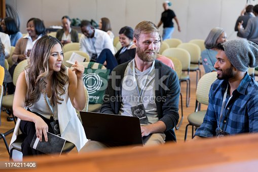 Young adults attend a conference together. A young man is using a laptop while talking with his friends.