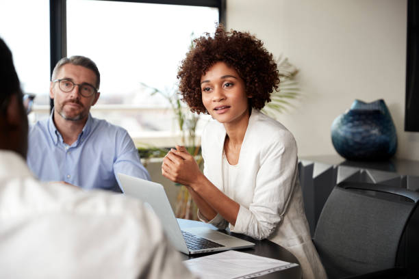 Millennial black businesswoman listening to colleagues at a corporate business meeting, close up Millennial black businesswoman listening to colleagues at a corporate business meeting, close up listening stock pictures, royalty-free photos & images