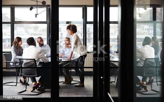 Millennial black businesswoman stands addressing colleagues at a meeting, seen through glass wall