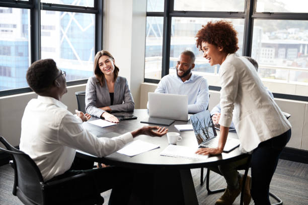 Millennial black businesswoman stands listening to corporate colleagues at a meeting, close up Millennial black businesswoman stands listening to corporate colleagues at a meeting, close up monkeybusinessimages stock pictures, royalty-free photos & images