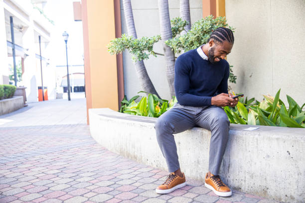 Millennial Black Man Depositing Check with Smartphone Young black man depositing a paycheck with his phone. bank deposit slip stock pictures, royalty-free photos & images