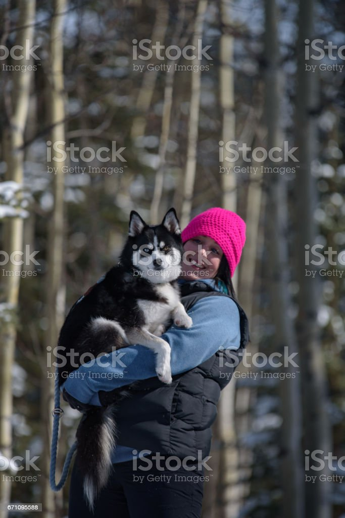 Millennial body positive woman holding cute dog in winter stock photo